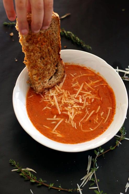A white bowl containing Tomato and White Bean Soup topped with Parmesan cheese, hand dipping in a grilled cheese sandwich.