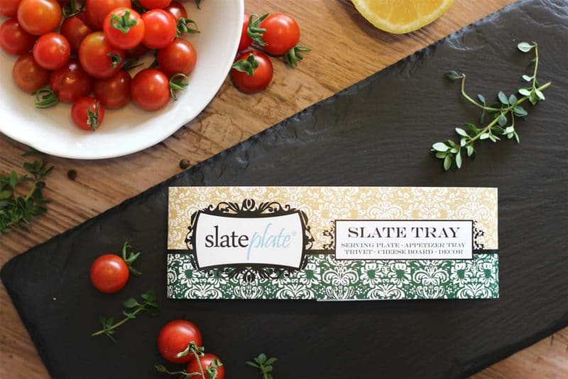 A black Slate Tray sitting on a wooden table, heirloom tomatoes, lemon and thyme sprigs in the background.
