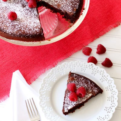A slice of Flourless Chocolate Torte topped with powdered sugar and raspberries on a white lace plate, silver fork on side.