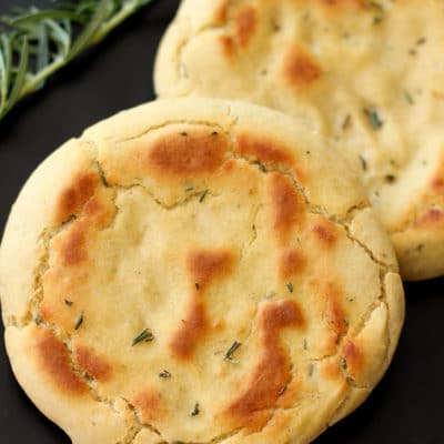 2 Rosemary and Garlic Flatbread rounds sitting on a black table, rosemary and garlic in background.