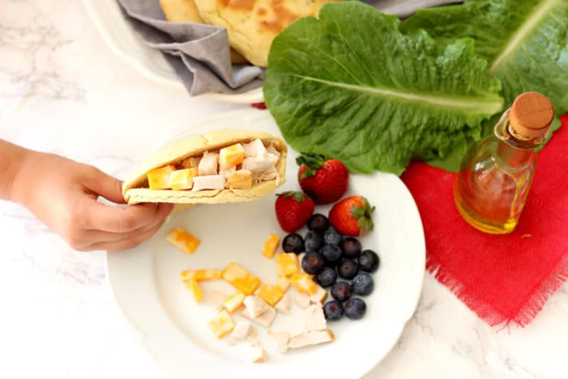 Sliced Rosemary and Garlic Flatbread pita filled with turkey and cheese, blueberries, strawberries and lettuce on side.