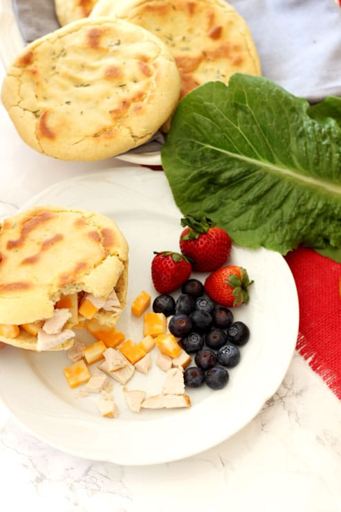 Sliced Rosemary and Garlic Flatbread pita filled with turkey and cheese with a bite taken out, side of blueberries, strawberries and lettuce.