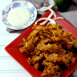 A red square plate of Bhaji and Onions next to bowl of ranch dipping sauce.