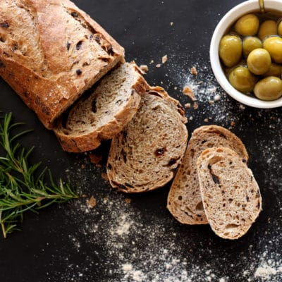 Sliced Rosemary Olive Bread sitting on a black table, olives and rosemary on side.