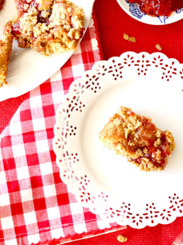 A white plate with a granola crumble square next to a larger plate with more granola crumble squares.
