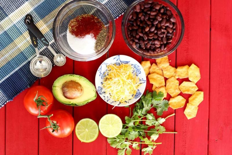 Ingredients for nachos on a red table, bowl of beans, seasonings, cheese, avocado, and chips.