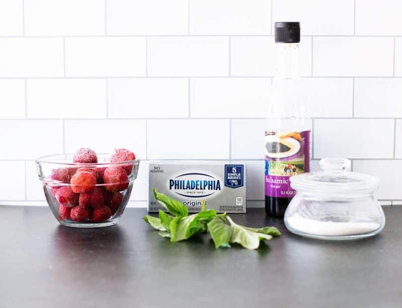 Frozen strawberries, cream cheese, basil, balsamic vinegar, and sugar on granite counter.