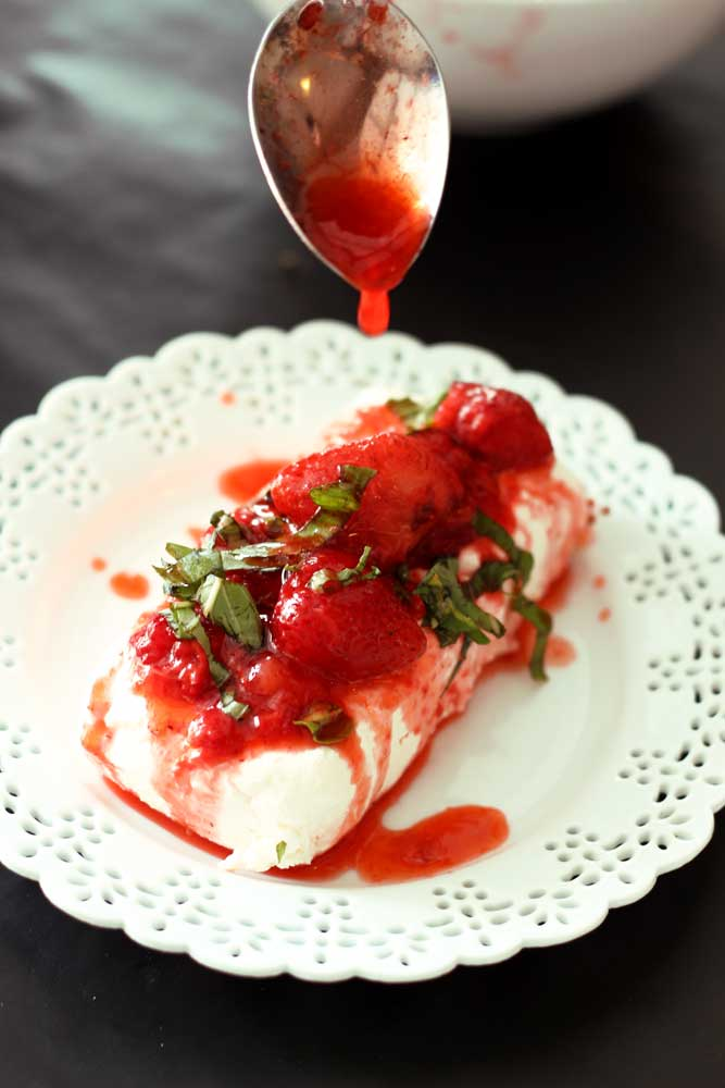 White laced plate sitting on a black table containing Basil Strawberries Cream Cheese, spoon dripping strawberry sauce.