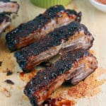 Wooden table containing 3 BBQ ribs, green ramekin with BBQ sauce and brush.