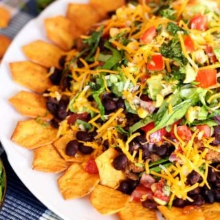 A close up of chips covered with nacho ingredients on a white plate.