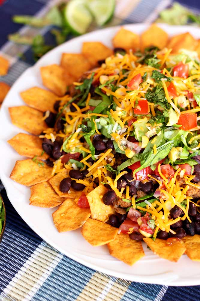 This is a plate of Gluten Free Nachos. Contains beef, beans, cheese, lettuce. Recipe from recipesworthrepeating.com