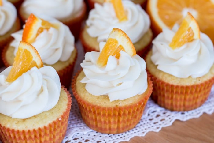 Five Orange Creamsicle cupcakes sitting on a white lace doily, topped with vanilla frosting and an orange slice.