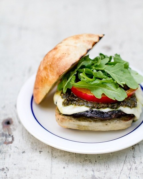White plate with a blue edge containing a portabella mushroom burger topped with pesto sauce, tomato, lettuce and a ciabatta bun.