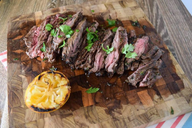 Wooden cutting board topped with skirt steak cooked medium topped with fresh parsley, squeezed lemon on side.