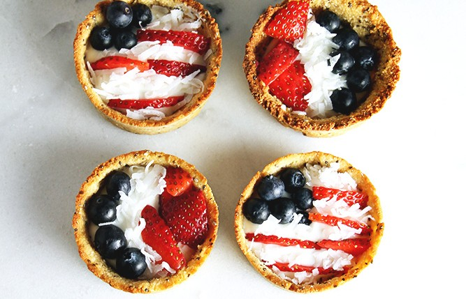 4 patriotic tartlets sitting on a white table, topped with coconut, blueberries and strawberries.