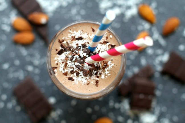 A chocolate smoothie topped with shredder chocolate and coconut with two straws.