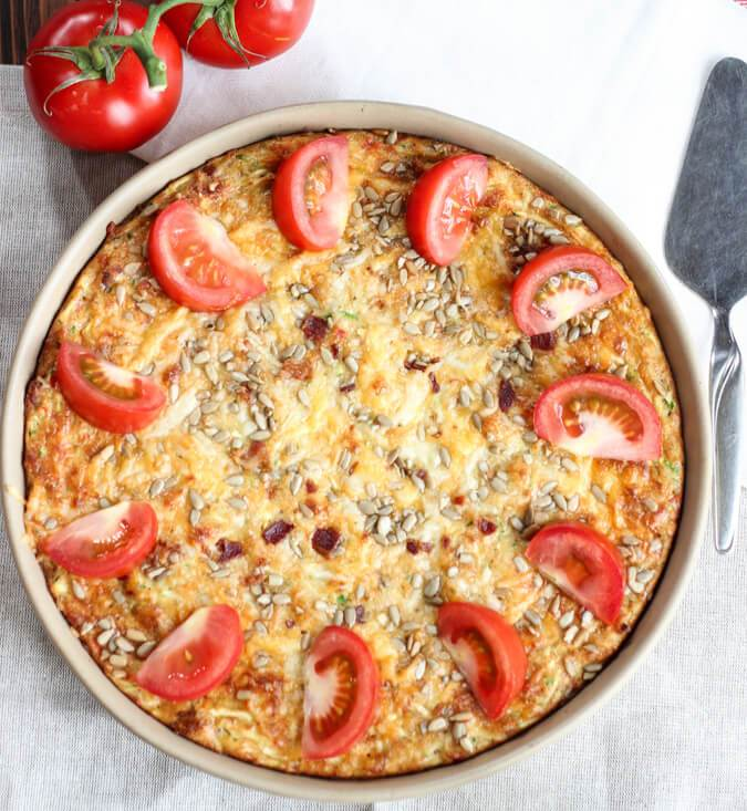 A close up of a round quiche with sliced tomatoes on top