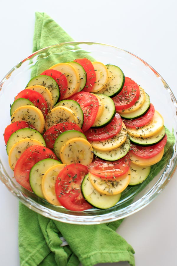 A plate of sliced squash and tomatoes on a white table