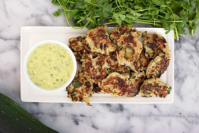 A white serving tray of zucchini chicken and dipping sauce