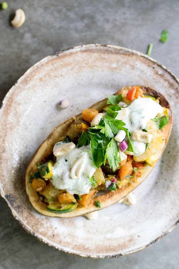 A close up of a loaded potato chaat on a rustic plate