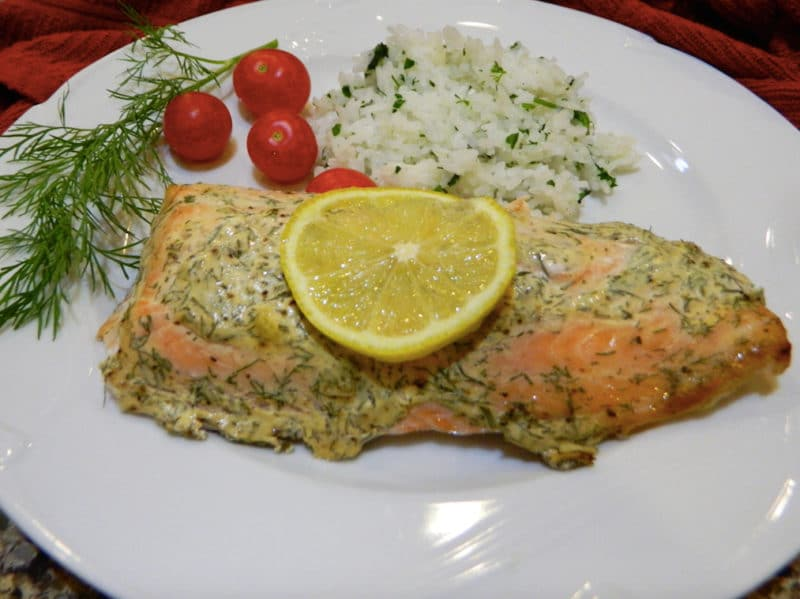 White plate containing Roasted Salmon with Dijon Dill Sauce with a side of cilantro lime rice, heirloom tomatoes on side.