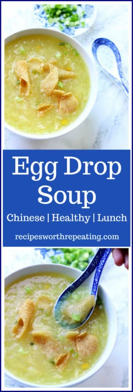 White bowl containing egg drop soup, spoon and dish with chopped scallions sitting on white marble table.