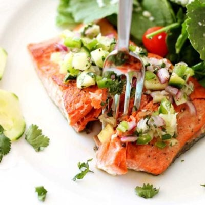 Pan Seared Salmon topped with a cucumber lime salsa, fork in salmon.