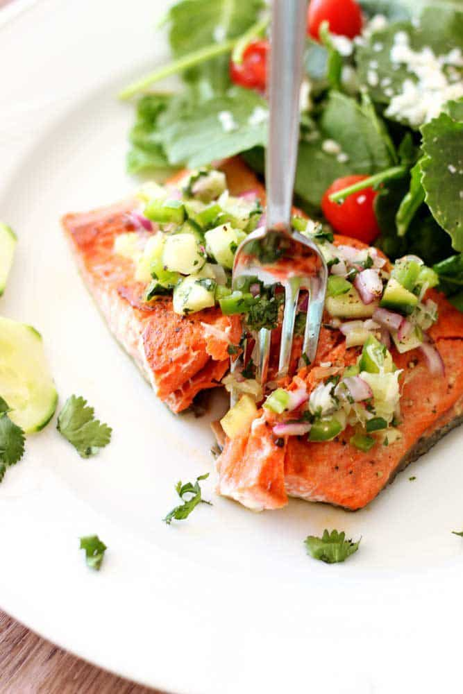 Pan-Seared Salmon topped with a cucumber lime salsa, fork in salmon.