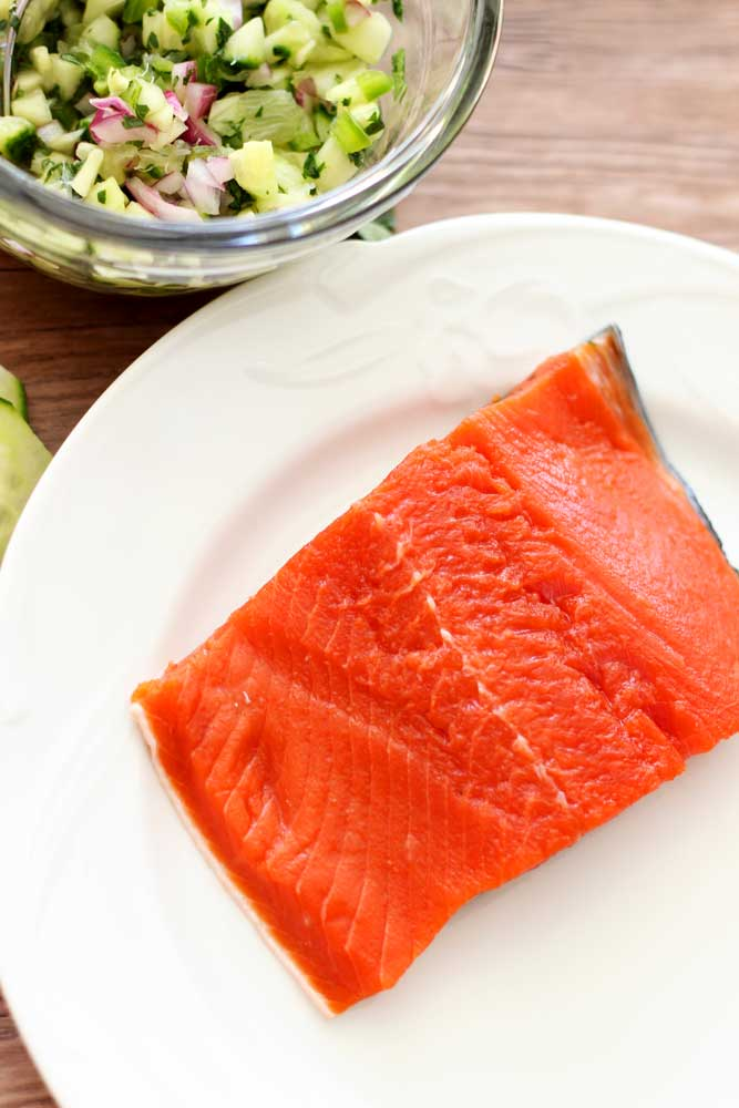Filet of Raw Sockeye Salmon sitting on a white plate, cucumber lime salsa in bowl.