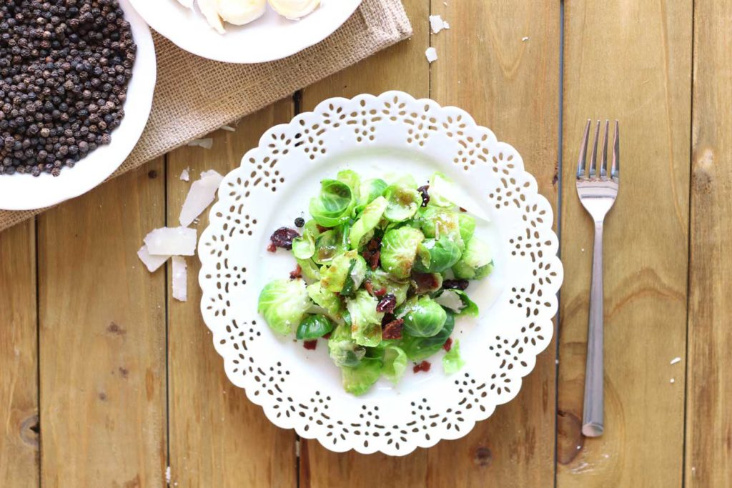 White laced plate containing a Brussels Sprouts salad sitting on a wooden table, fork on table.