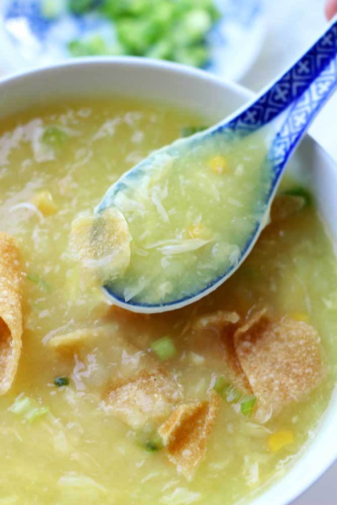 White bowl containing egg drop soup topped with crispy chinese wontons, spoonful of soup.