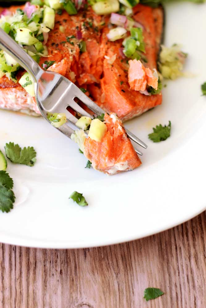 A fork containing fresh Pan-Seared Salmon topped with cilantro lime salsa.