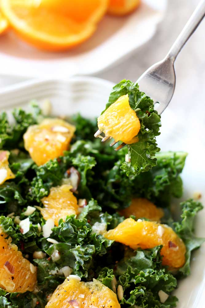 A plate of orange and kale salad on a fork