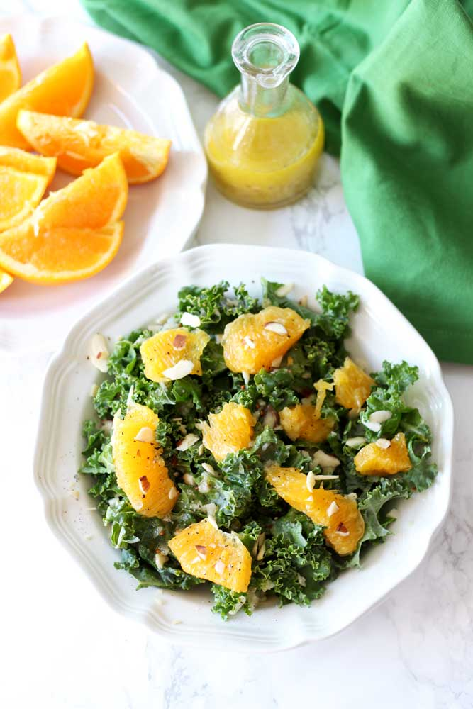 An orange and kale salad on a white plate