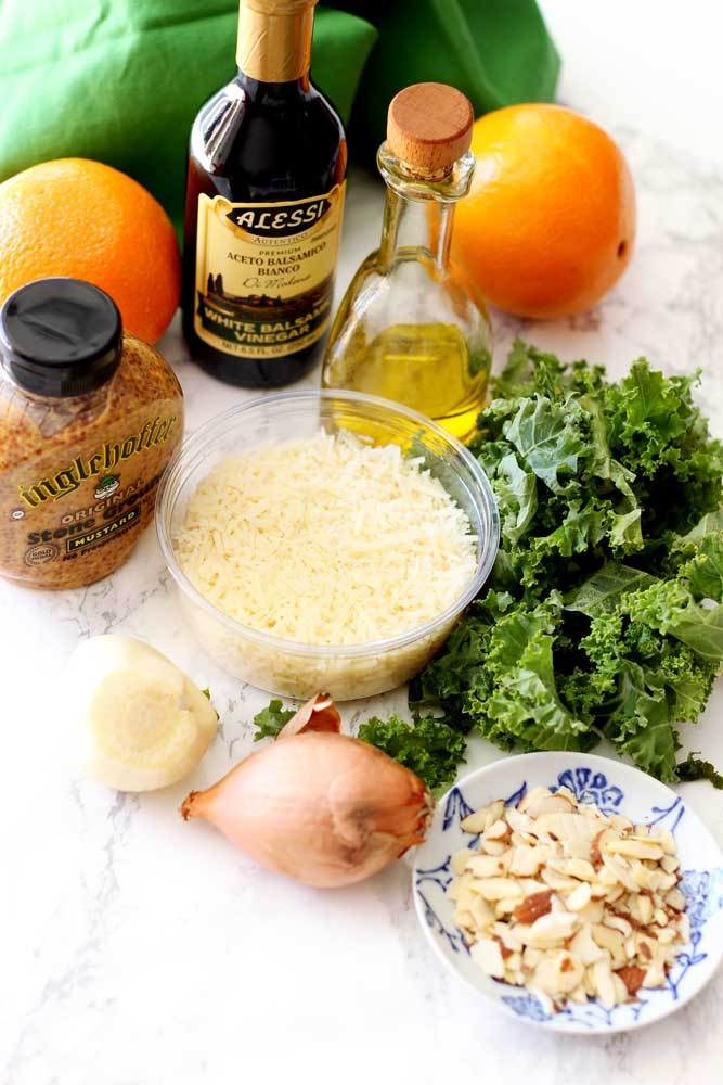 A table with kale, olive oil, mustard, garlic bulb, and white balsamic vinegar