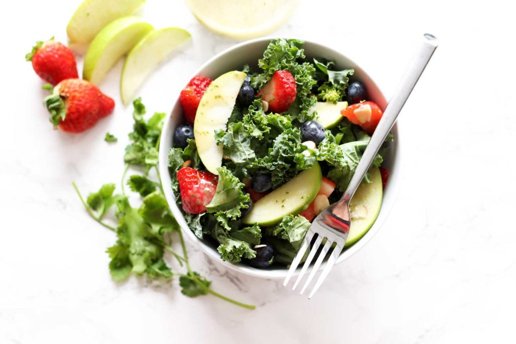 White bowl containing kale salad topped with fresh strawberries, green apples and blueberries sitting on a white table, fork on top of bow.