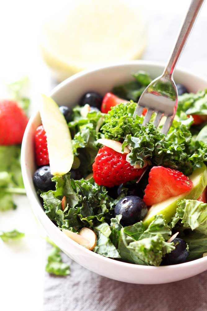 White bowl containing Apple and Berry Chopped Kale Salad, fork containing strawberry, kale and almond.