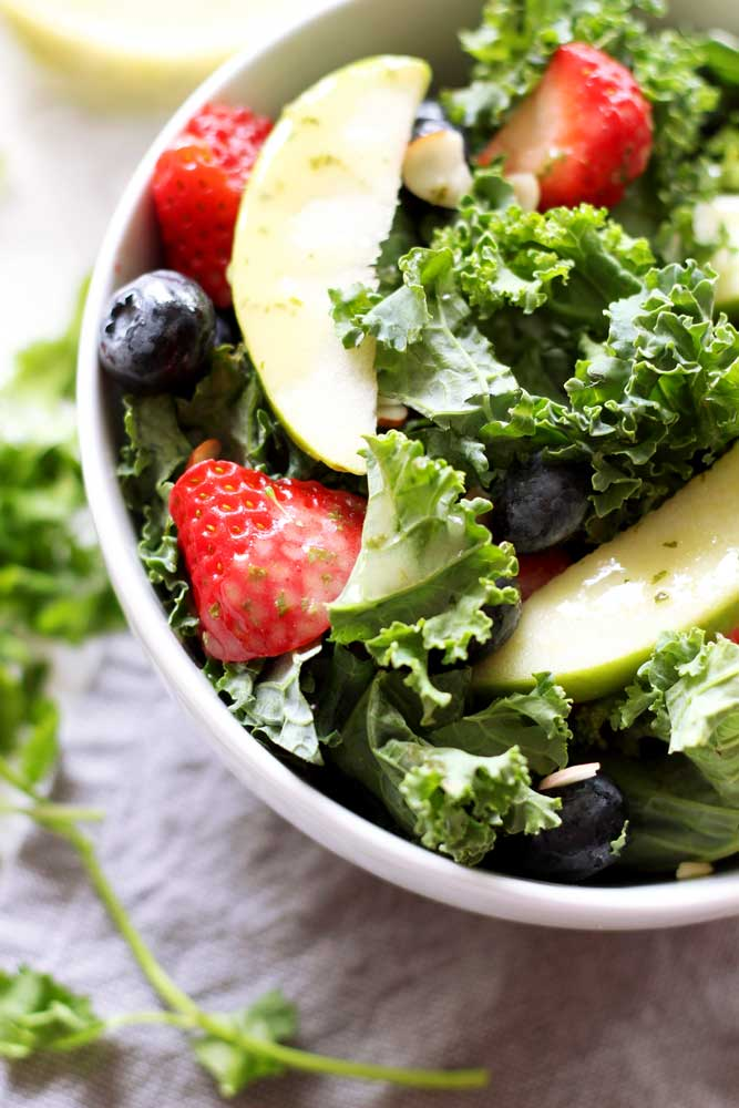 White bowl containing Apple and Berry Chopped Kale Salad, topped with a basil vinaigrette dressing.