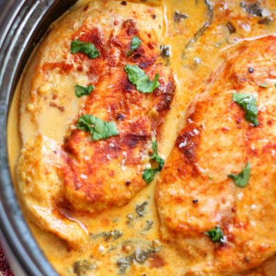Black pan containing 3 Lemon Butter Chicken Breasts, crossed spoons and lemon slices on table.
