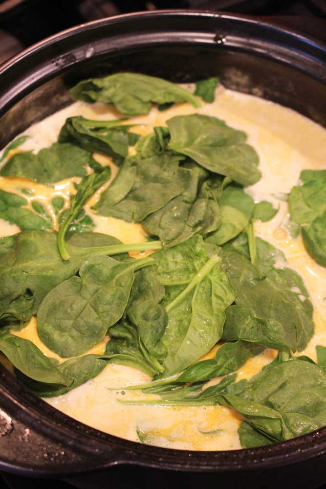 Black pan containing lemon butter cream sauce with fresh spinach.