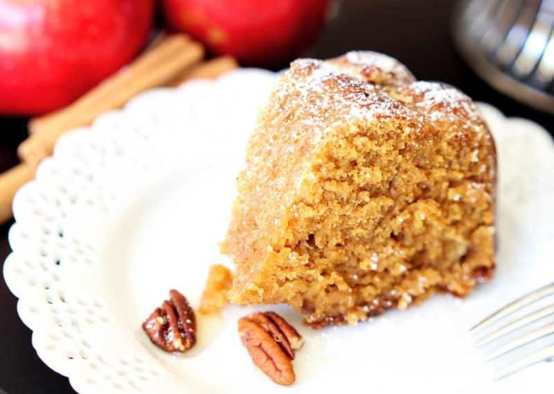 A piece of sliced apple pumpkin bundt cake sitting on a white lace plate, 2 pecans and a fork on plate.
