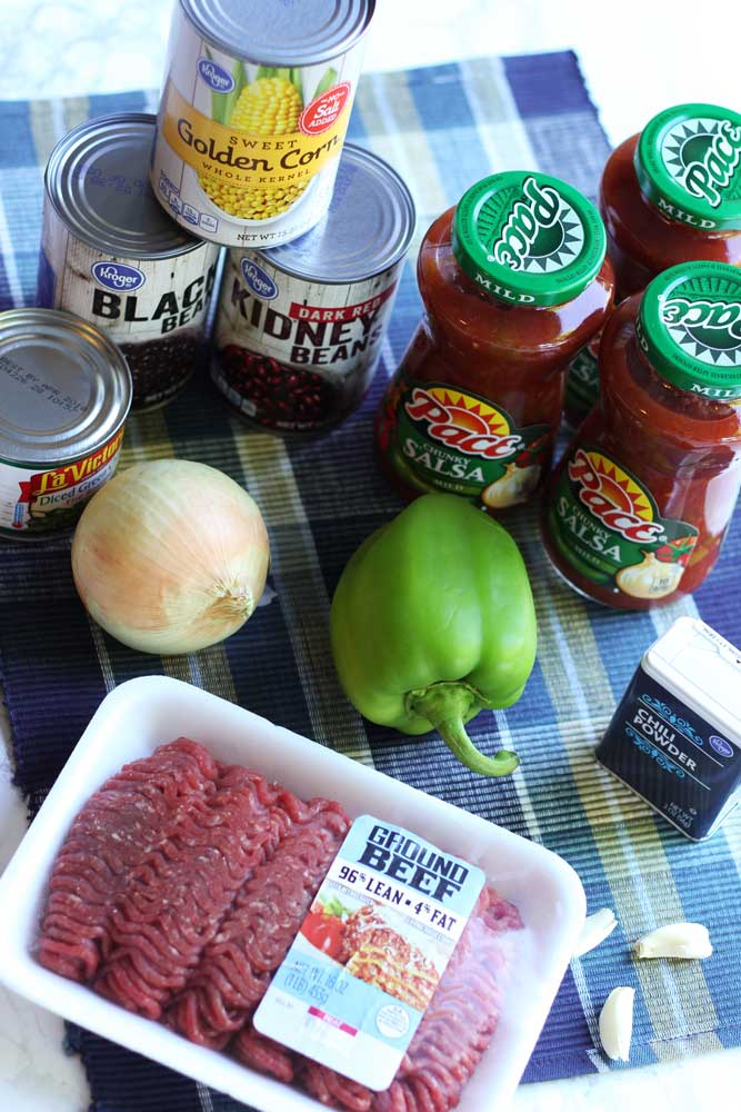 Ingredients for Southwest Chili that includes Hamburger meat, beans, corn, onion, pepper and salsa on table.