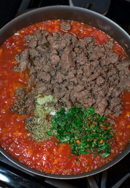 Skillet containing marinara sauce, ground beef, and fresh herbs.