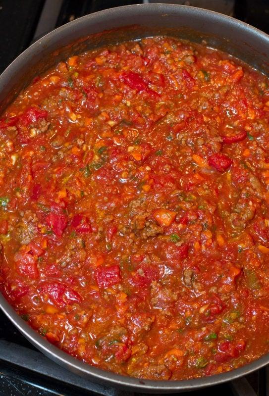 Homemade marinara sauce in a skillet simmering.