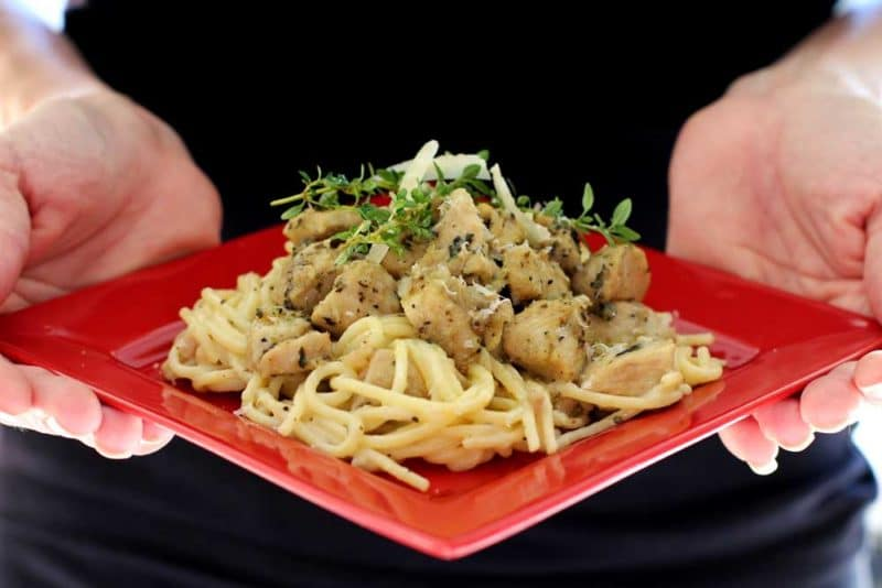 Person holding a red plate with 2 hands that contains Garlic Basil Chicken Pasta topped with fresh thyme sprigs and shaved Parmesan cheese.