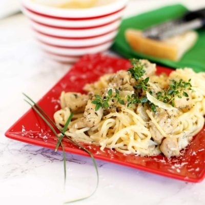 Red plate containing Garlic Basil Chicken Pasta topped with fresh thyme and Parmesan cheese.