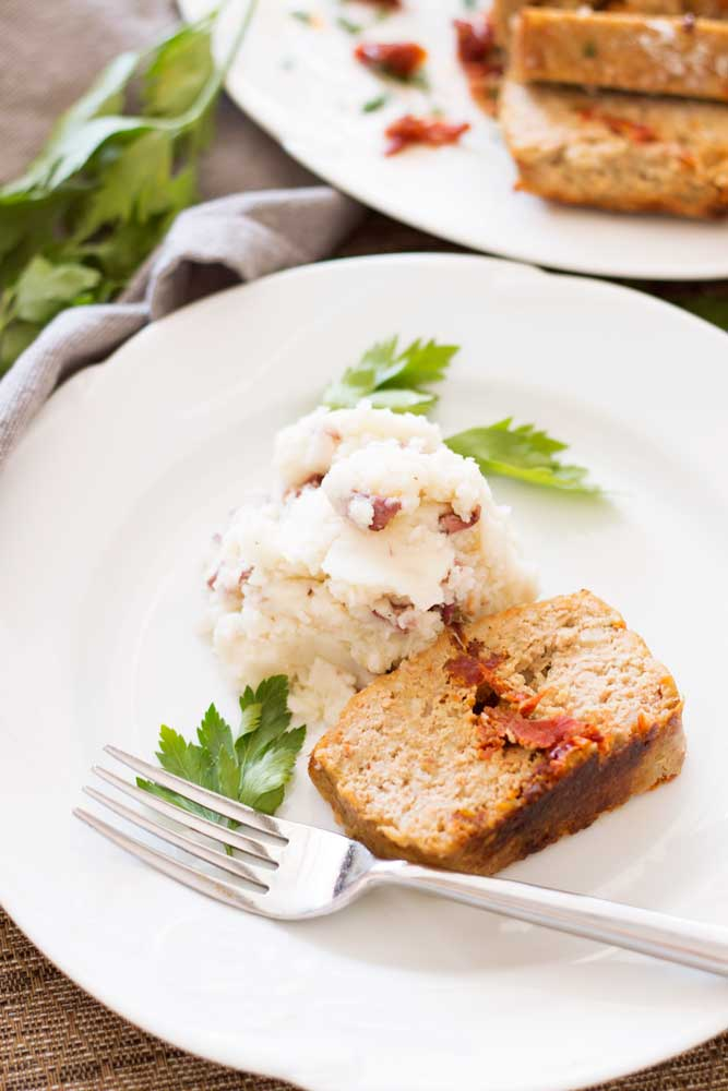 White plate containing a slice o turkey meatloaf with sun-dried tomatoes, side of mashed potatoes.