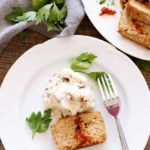 White plate containing Feta and Sun-Dried Tomato Meatloaf with mashed potatoes.