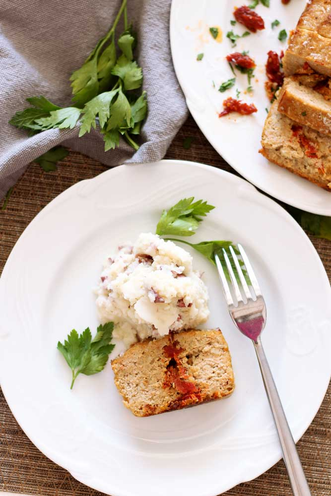 White plate containing Turkey meatloaf with Sun-Dried Tomato Meatloaf with mashed potatoes, fork on side.