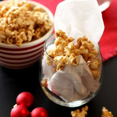 Bowl of Bourbon Caramel Popcorn sitting on a black table, red Christmas balls on table by red tablecloth.